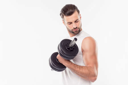 Successful, attractive, sporty, athletic person lifting weights with hand, arm, looking at his relief biceps, isolated on white background