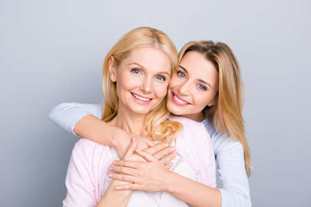 Portrait of stylish cute attractive charming mother and daughter, family with one single parent, warm hugs, looking at camera isolated on grey background