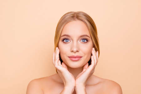 Big eyed, charming, pretty, cute, lovely girl enjoying her perfect face skin after mask, lotion, peeling, cream, balm, holding hands on cheek, isolated on beige background, wellness wellbeing concept