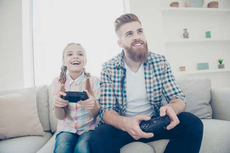 Cheerful joyful excited stylish trendy father and daughter holding joy-sticks in hands playing video game sitting on couch indoor in living room enjoying free time wearing casual outfit front view