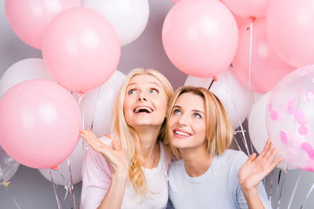 Wow, portrait of surprised amazed charming mother and daughter admire enjoying decorations white pink air balloons looking up having festive mood pleasure isolated on grey background