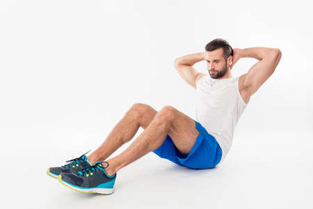 Full size portrait of active, athletic, sporty, attractive, confident guy making, showing abdominal crunches, having two hands, arms behind the head, isolated on white background Stok Fotoğraf
