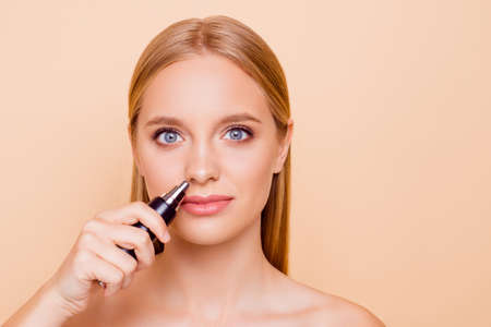 Portrait of natural nude stylish trendy model with flawless skin using special machine on batteries for getting rid on unwanted hair in nostril isolated on beige background looking at camera