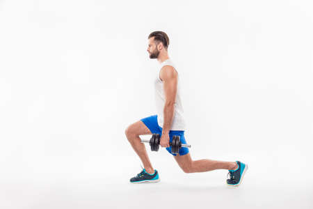 Full size, side view portrait of successful, professional, attractive, concentrated man showing how to make lunges front, back with weight, isolated on white background Stock Photo