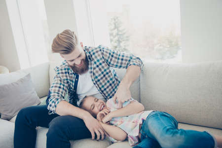 Family with one parent, stylish father with good humor kidding with excited laughing daughter on sofa in living room happy moments dreamday funny game babysitting Stock Photo