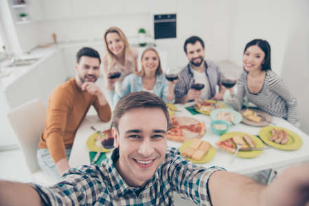 Handsome, attractive, stylish man making self portrait with best friends on blurred background sitting at the table holding glasses with red wine, celebrating holiday indoor