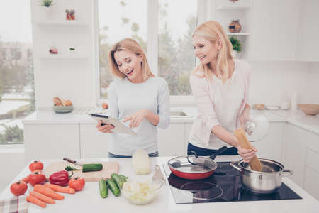 Cheerful creative attractive housewives preparing homemade dinner boil macaroni vegan salad using gadget frying pan dish, searching menu in internet, standing in modern white kitchen with interior Stockfoto - 104230839