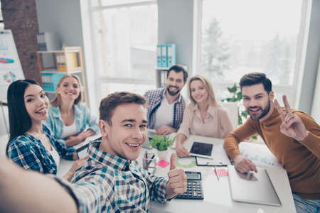 Self portrait of cheerful, positive, stylish, confident, attractive financiers shooting selfie on front camera showing two fingers, thumb up with hands having relax, rest, pause, break, timeout Stock Photo