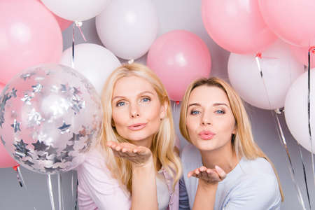 Lovely cute flirting tempting seductive sexy friendly mother and daughter sending kiss with pout lips and hand at camera having white pink decorations air balloons around isolated on grey background
