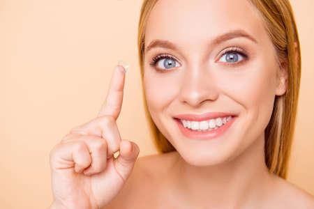 Schließen Sie herauf Porträt des hübschen, charmanten, niedlichen, fröhlichen, positiven, fröhlichen, nackten, natürlichen Mädchens mit strahlendem Lächeln, das kristalline Linse auf Zeigefinger gestikuliert, lokalisiert auf beigem Hintergrund