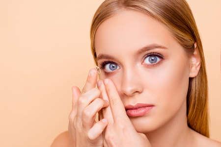 Porträt des hübschen, charmanten, nackten, natürlichen Mädchens, das kristalline Linse in rechtes Auge mit Zeigefinger setzt, die Kamera lokalisiert auf beigem Hintergrund betrachtet