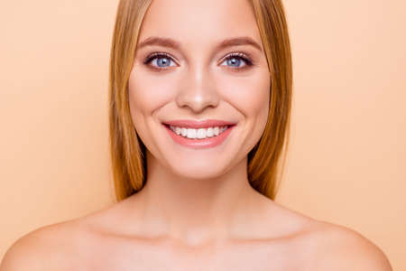 Close up cropped portrait of pretty, charming, positive, cheerful girl with beaming smile with perfect smooth soft silk face skin isolated on beige background, wellbeing, wellness concept