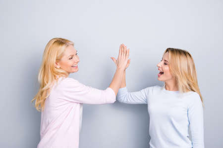 Give me high five, mother and daughter celebrating victory win, holding palms together clapping hands, winners shouting, screaming, isolated on grey background