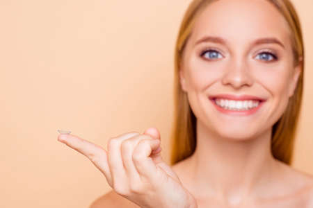 Portrait of pretty, charming, cheerful, positive, joyful, toothy girl on blurred background holding focused crystalline lens on index finger isolated on beige background Stockfoto