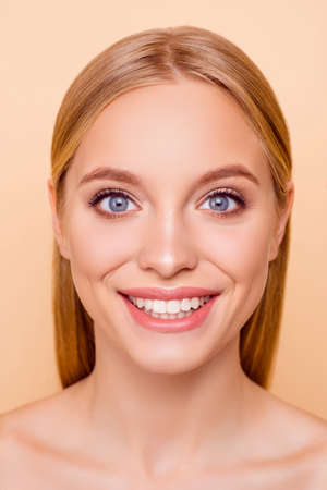 Close up vertical portrait of toothy pretty, charming, cheerful, gorgeous glad girl with soft smooth perfect skin after vitamins detox mask peeling lifting scrub isolated on beige background