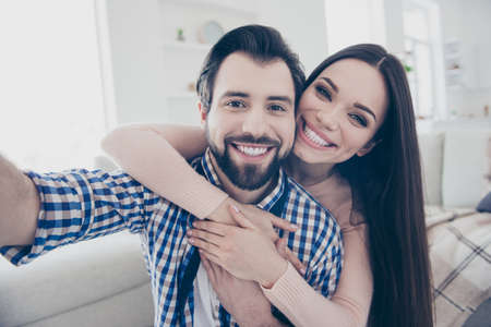 Self portrait of funny foolish couple in casual outfits bearded man carrying his lover on back shooting selfie on front camera indoor Stok Fotoğraf
