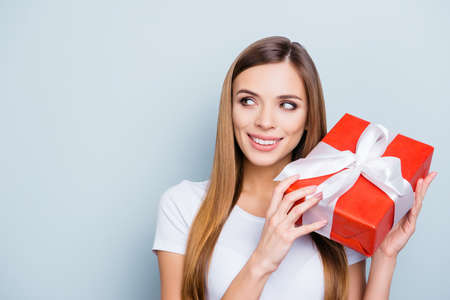 Portrait with copyspace empty place of nice gorgeous girl holding gift box in red package with white ribbon near ear want to know what inside isolated on grey background