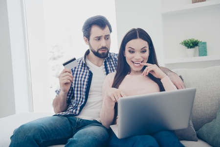 Portrait of bearded worried man having plastic credit card in hand looking at his glad girlfriend making a lot of purchase in internet spending much money buying many goods crazy buyer Stock Photo