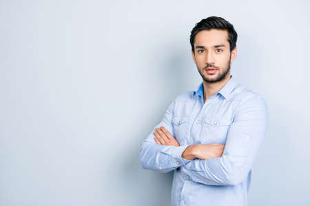 Portrait with copyspace empty place for advertisement of half-turned virile man with black hair holding arms crossed looking at camera isolated on grey background Stock Photo