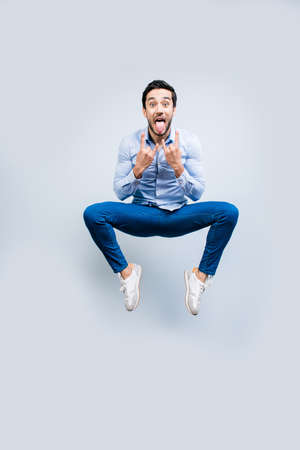 Portrait of crazy man funny creative guy in jeans sneakers jumping in air gesturing rock and roll signs with two hands showing tongue out isolated on grey background, joy pleasure concept