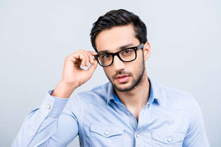 Head shot portrait of tempting seductive man with black hair in glasses holding eyelet of spectacles on his face virile sight looking at camera isolated on grey background