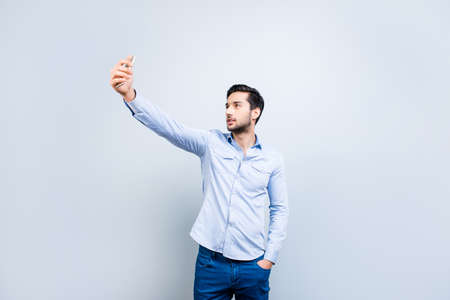 Portrait of trendy narcissistic stylish man holding hand in pocket of pants using smart cell phone shooting self picture on front camera isolated on grey background