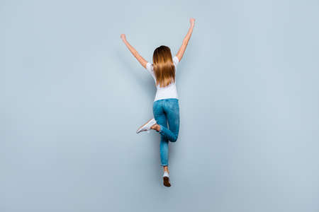 Full length rear view portrait of pretty slim fit girl jumping with hands up raised leg isolated on grey background enjoying summer time