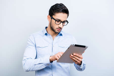 Portrait of busy man in blue shirt using wi-fi internet having tablet in hands texting massage checking email isolated on grey background, technology electronic wireless devices concept