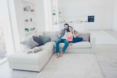 Full size portrait of stylish positive couple sitting in modern white apartment using console looking comedy funny channel program film on television hugging embracing eating snack Zdjęcie Seryjne