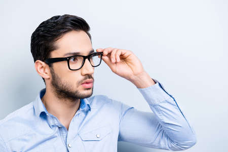 Portrait of virile trendy bachelor with black hair in blue shirt casual outfit looking away holding eyelet of glasses on face isolated on grey background