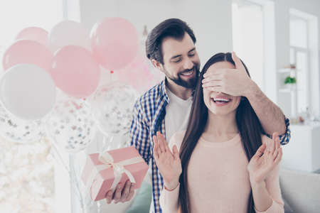 Portrait of bearded cheerful man closing eyes with palm to lover prepare pink packed gift box case, air ballons, sweet attractive cute couple celebrating valentine day, 14-february