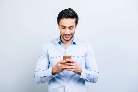 Portrait of cheerful man chatting with girlfriend, using 3G, wi-fi internet, having, smart phone cellphone in hands, surfing, isolated on grey background, technology concept