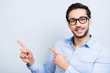 Portrait with copyspace, cute smiling man with black hair in glasses indicate showing empty place with two forefingers looking at camera isolated on grey background, direction way decision concept