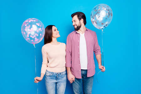 Portrait of pleased joyful couple holding hands looking at each other having air balloons in arms enjoying meeting isolated on vivid blue background