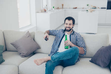 Portrait of positive cheerful single man with stubble in jeans shirt choosing channel with console watching football match comic funny program drinking lager