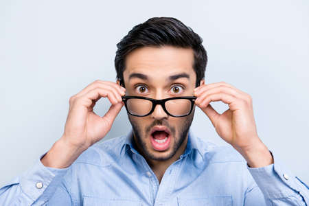 Head shot of shocke  funny guy with black hair wide open mouth big-eyed looking out glasses on face isolated on grey background