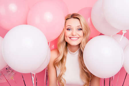 Portrait of cheerful childish girl with many white air balloons around looking at camera isolated on pink background
