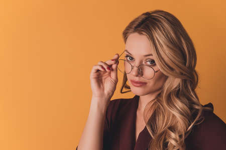 Portrait with copy space empty place of clever confident woman in burgurden suit looking out glasses on her face at camera isolated on dark yellow background