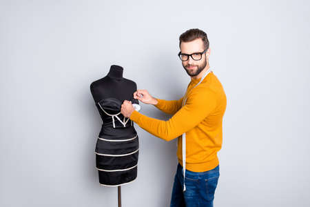 Portrait of attractive nice dressmaker in sweater and jeans with centimeter on neck taking measurements from dress on mannequin with needles looking at camera isolated on grey background