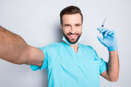 Self portrait of joyful cheerful man with stubble and sterile, protective face mask shooting selfie on front camera having showing syringe in hand, isolated on grey background