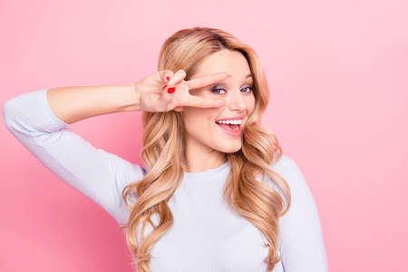Hey! Portrait of carefree friendly girl with modern hairdo gesturing v-sign near eye looking at camera isolated on pink background