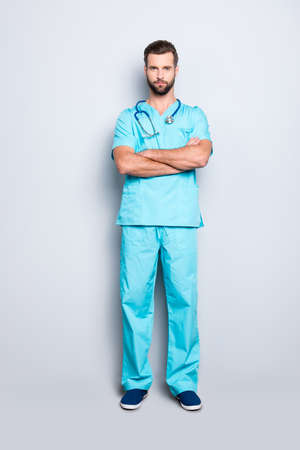 Full size body portrait of brutal virile man with stethoscope on his neck in blue lab uniform, holding his arms crossed, isolated on grey background