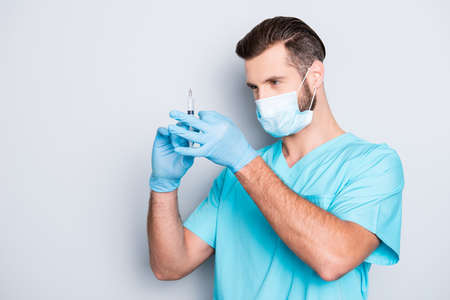 Portrait of busy serious medic with hairstyle in lab blue uniform and sterile mask checking, preparing vaccine having syringe in hands, isolated on grey background