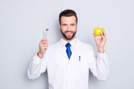 Portrait of successful toothy dentist in white lab coat, blue tie, holding equipments and green apple in hands, isolated on grey background, recommend taking care about teeth Stock Photo