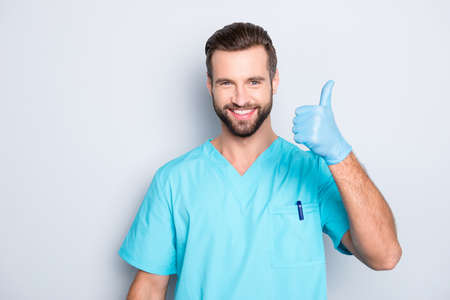 Portrait of joyful positive medic with stubble in lab blue uniform looking at camera showing thumb up sign with hand, finger, isolated on grey background, advertisement concept
