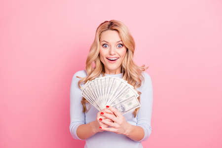 Portrait of astonished surprised big eyed girl, jack-pot casino player, holding fan of much money in hands isolated on pink background