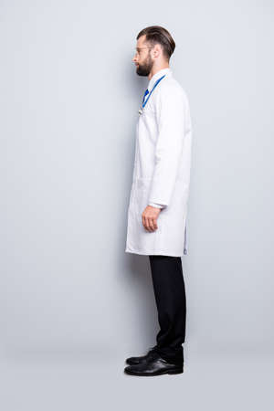 Full size half face fullbody portrait, snap of  virile harsh bearded doc in white lab coat and stethoscope on his neck, isolated on grey background Stock Photo