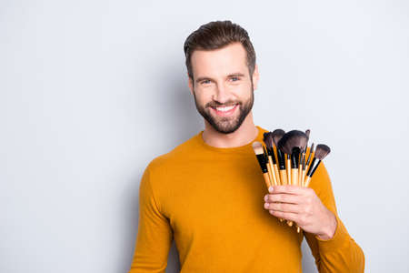 Portrait of handsome cheerful visagist with stubble in sweater having verity of brushes in arm, looking at camera, standing over grey background Stock Photo
