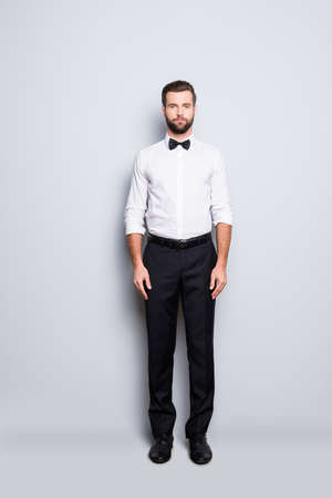 Full size fullbody portrait of serious handsome croupier in white shirt, bowtie, black pants, formalwear, looking at camera, isolated on grey background Stock fotó