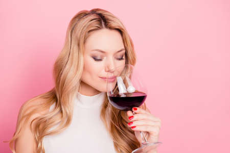 Portrait of lovely cute girlfriend with close eyes natural make up having glass with beverage, tasting dry semi-sweet red wine keeping eyes closed isolated on pink background